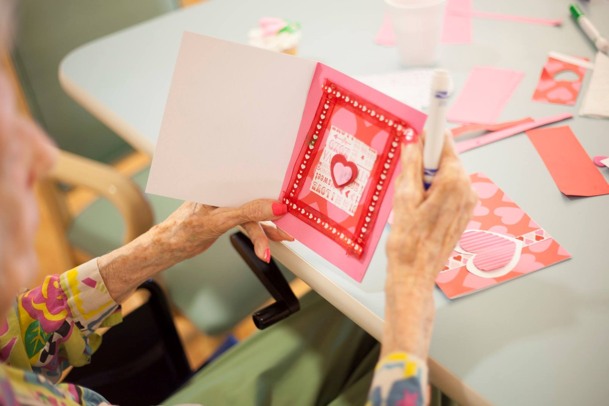 Senior woman enjoys an afternoon making Valentine's Day cards